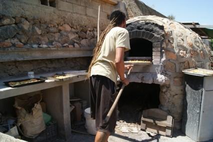 Raúl saca del horno una pizza para los asistentes a una de las jornadas