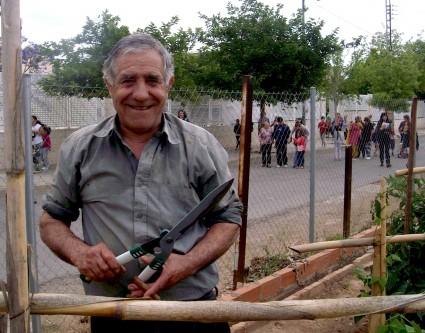 Uno de los hermanos Herráiz. Tras él el colegio público desinteresado en la experiencia agrícola de los yayo okupas.