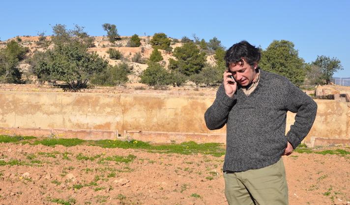 Enric asegura que un agricultor moderno tiene que ir con la azada en una mano y el móvil en la otra. Detrás de él, la colina donde se encuentra el yacimiento ibérico del Tos Pelat
