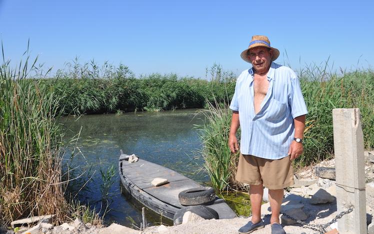 José Ballester, El Curro, junto a la barca enla que a veces sale a pescar anguilas conmornell.