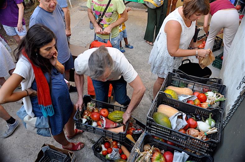 El agricultor eco de Huerto Aspero atiende a sus clientes en el local de distribución semanal de Gines.